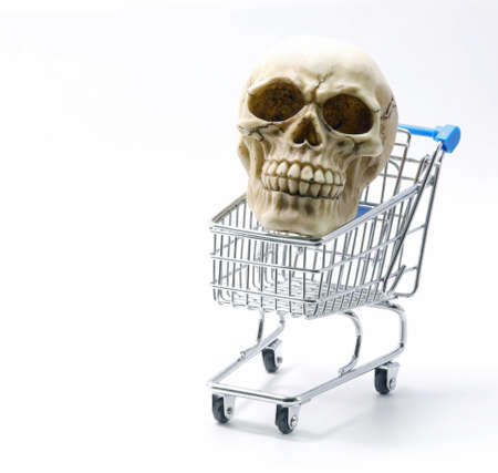 human skull with teeth on a shopping cart and white background Stock Photo