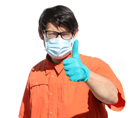 doctor with surgical mask make the thumbs up sign to indicate victory over the coronavirus