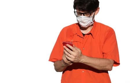 young doctor in a mask surgically uses his cellphone to send a message on white background
