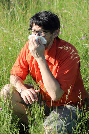 young boy you had and sneezes with a handkerchief because he is allergic to pollen in the middle of the lawn in summer