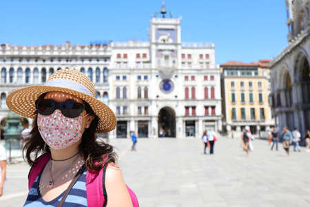 Beautiful tourist woman with red surgical mask and straw hat and black sunglasses in the island of Venice in Italy during the lockdown caused by the Corona Virus