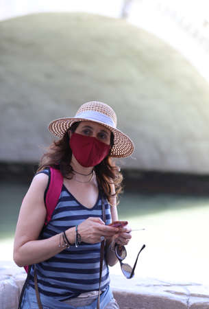 Young woman with surgical mask and straw hat while travelling the city