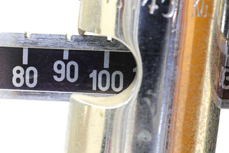 Ancient bathroom scale with the number 100 on a white background