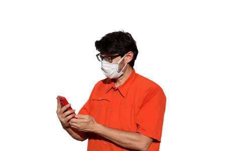 man with orange shirt and surgical mask while using smarthpone to send messages on a white background