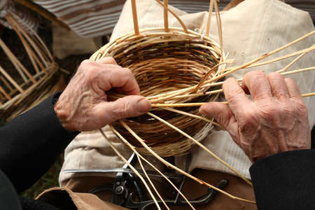 hands of the elderly craftsman while weaving a wicker basket at the market