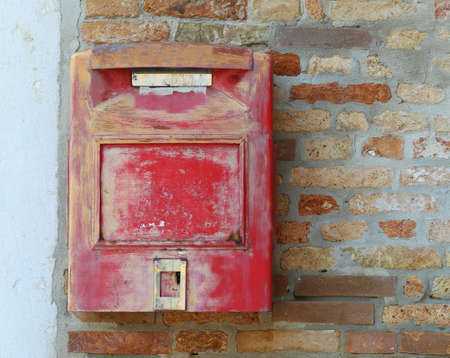 mailbox of red color on the brick wall