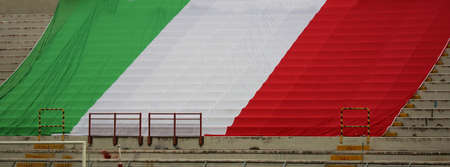 huge Italian national flag with Il Tricolore white red green on the empty stands during a game without public due to the coronavirus