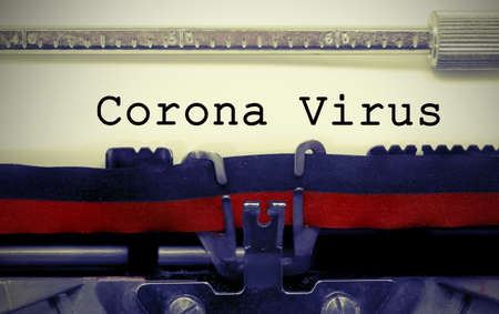 Corona Virus text on white sheet in vintage typewriter with black and red ink ribbon Foto de archivo