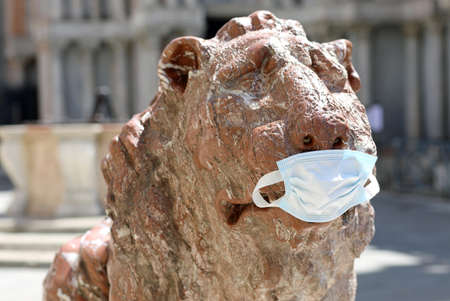 Venice, VE, Italy - May 26, 2020: Statue of Lion in Venice in Surgical Mask during lockdown by Corona virus in Italy Editorial