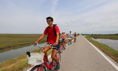 cheerful family cycling pedals on the bike path near the island of Venice in summer Foto de archivo