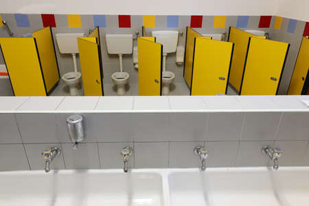 long sink with four taps inside a kindergarten with toilets with yellow doors without children Foto de archivo