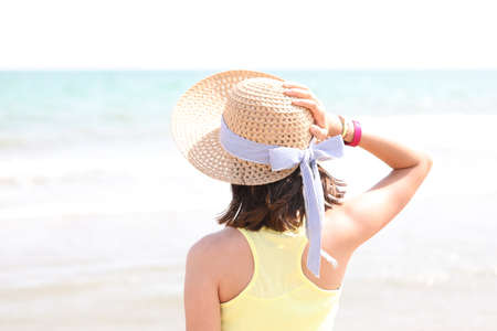 young girl on the seashore with straw hat and light tones of very bright photography