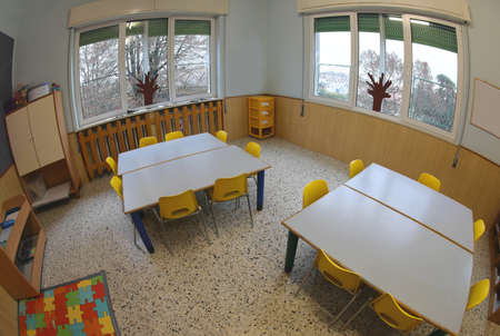 interior of a classroom of the nursery school without children and small tables and chairs