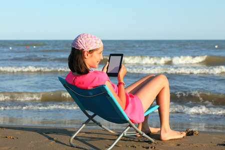 little girl on the seashore lying down while reading an electronic text from an e-book Foto de archivo