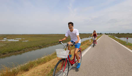 cheerful boy pedaling bicycle on bicycle path in summer with his mom