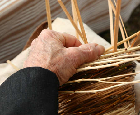 gnarled hand of the elderly craftsman mind weaves the children of a basket made of wicker to sell it to the local market