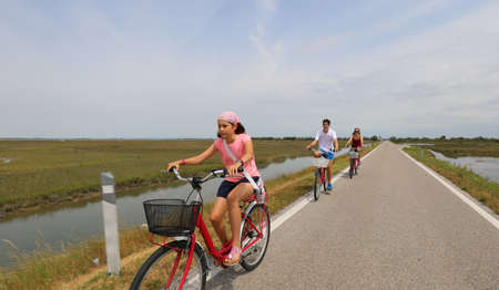 little girl pedaling a bicycle on the bike path together with her brother and mom in summer