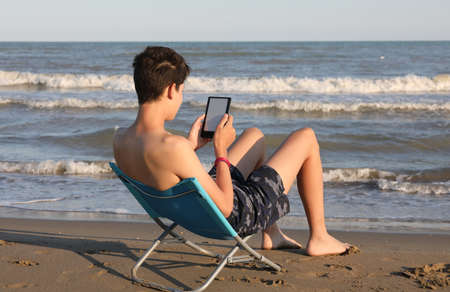 student while reading an e-book of his smartphone on the seashore in summer