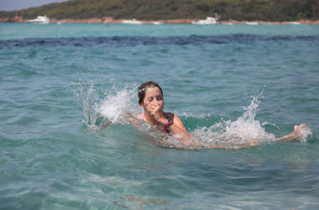 girl takes a dip in the beautiful water of the sea in summer Foto de archivo