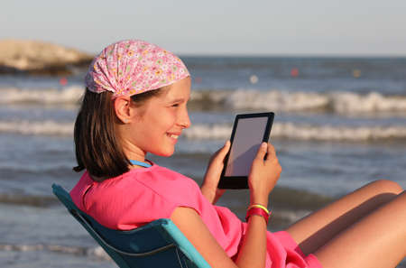 smiling girl while using a tablet on the beach shore in summer with a bandana on her head Foto de archivo