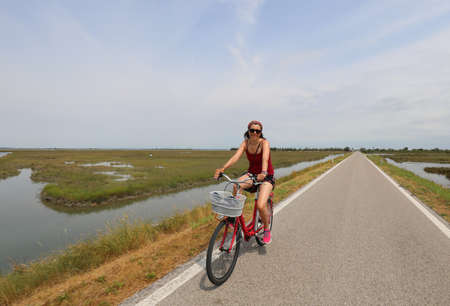 young woman pedaling on the bicycle in the bike path in the middle of the lagoon in summer
