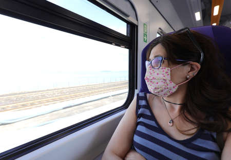 woman with long dark hair wears a mask while traveling by train observing the flowing landscape outside the window