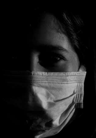 dramatic portrait of girl in half shadow with surgical mask in black and white