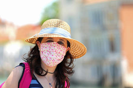 cute young woman with straw hat and big surgical mask to protect the respiratory tract of coronavirus in summer Foto de archivo