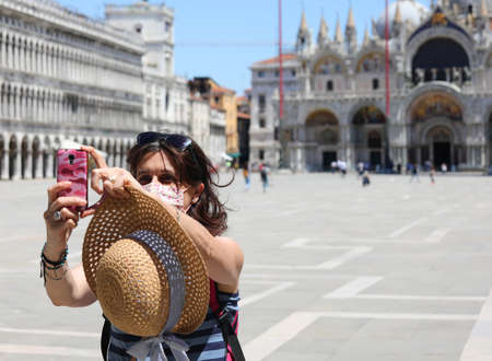 young woman takes a selfie in San Marco square with very few tourists due to the Lockdown caused by the coronavirus Foto de archivo