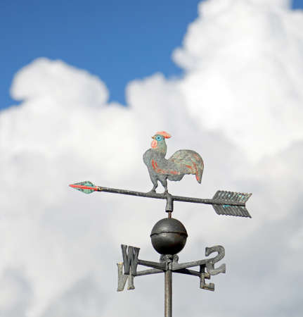 weather vane with the letters of the cardinal points and the arrow to indicate the wind direction with the background of blue sky and white big clouds