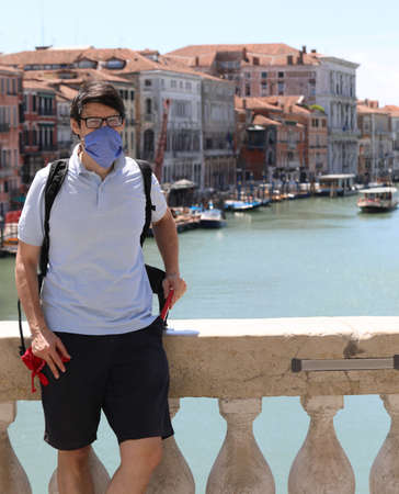 handsome guy on Rialto bridge with surgical mask to protect himself from coronavirus in Venice in Italy