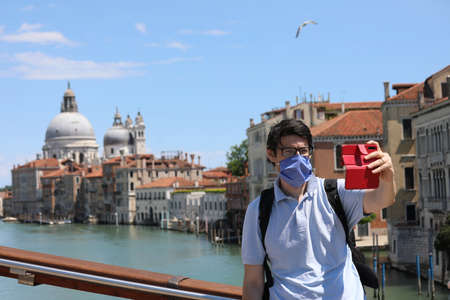 charming man with my hair and glasses wears surgical mask mind takes a selfie in the city of Venice during the coronavirus epidemic