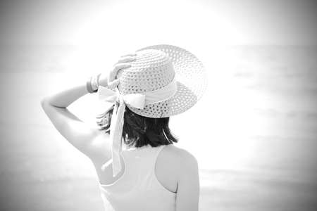 little girl on the seashore with hat and light tones Foto de archivo