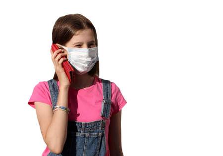 little girl Chat with smartphone dressed in dungarees and with surgical  mask to protect herself from the coronavirus during the terrible epidemic