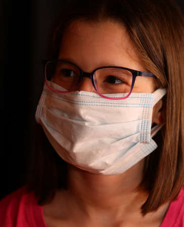 young girl with glasses wears the surgical mask to protect herself from the coronavirus epidemic