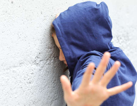 girl with hoodie trying to protect herself from the attacker with her hand Archivio Fotografico