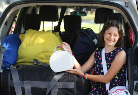 smiling girl puts her purse on the car before leaving on vacation Foto de archivo