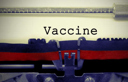 Vaccine text on white sheet in vintage typewriter with black and red ink ribbon