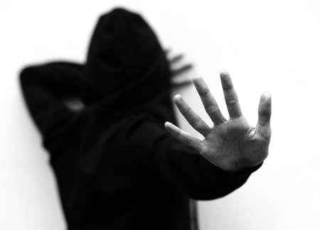 dramatic scene of the girl with hoodie trying to protect herself from the attacker with her hand with black and white effect
