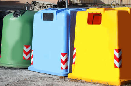 three colored dumpster to collect glass used paper and plastic material in the city