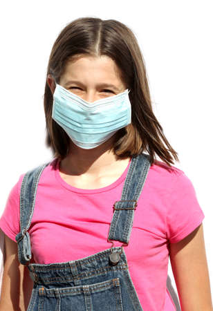 young girl with dungarees and surgical mask for protection from coronavirus during the world epidemic Stock Photo