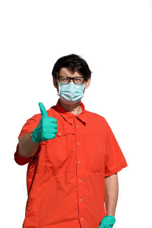 young man with orange shirt and lattex protective gloves and surgical mask makes the Ok sign that everything will be fine and the white background
