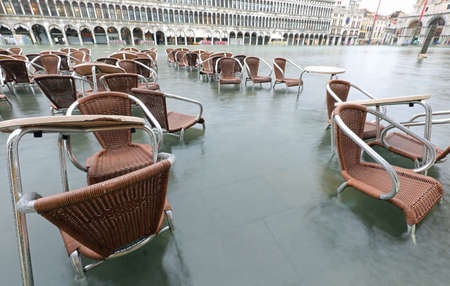 chairs and tables of alfresco cafe during tide in Venice in Italy Banco de Imagens