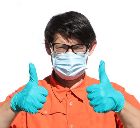 young bespectacled doctor with surgical mask and 2 thumbs raised on white background Stock Photo
