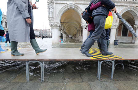 people with boot on the pedestian platform in Venice during tide Stock fotó