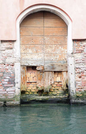 ancient door of a house in Venice in Italy ruined by water during high tides