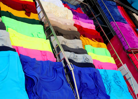 T-shirts and vests colored with fluorescent colors for sale in the market stall