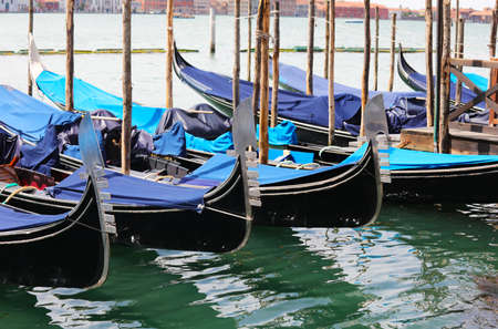 many gondolas moored in the Venice lagoon with the traditional symbol on the bow