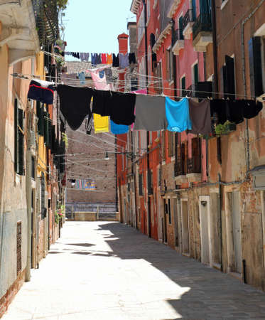 narrow street of the European city with clothes hanging out to dry in the sun without people in summer