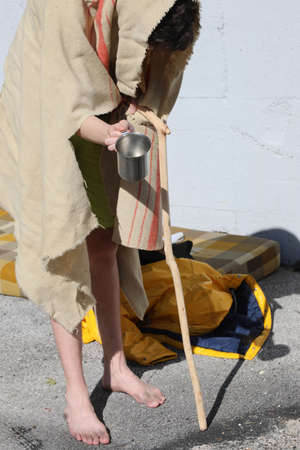 lame homeless man with a stick to walk the filthy blanket asks people in town for money